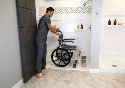 Roll-InBuddy Solo SB6w chair with caregiver in shower