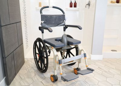 Roll-InBuddy Solo SB6w chair in front of shower with toilet aid