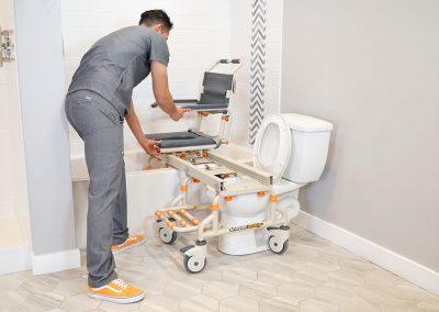 TubBuddy SB2 chair over bathtub with caregiver