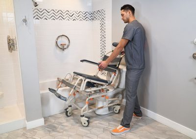TubBuddy Tilt SB2T chair over toilet tilted with caregiver
